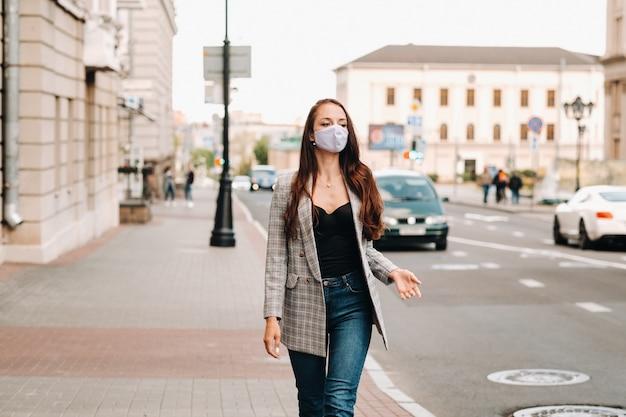Concetto di covid-19 e inquinamento atmosferico pm2.5. pandemia, ritratto di una giovane donna che indossa una maschera protettiva per strada. concetto di salute e sicurezza.