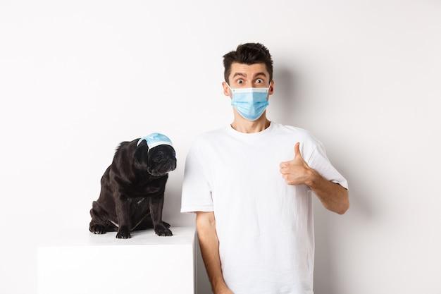 Covid-19, animali e concetto di quarantena. bel giovane e cane di piccola taglia che indossano maschere per il viso, proprietario che mostra il pollice in su in segno di approvazione, elogio del prodotto super cool, bianco