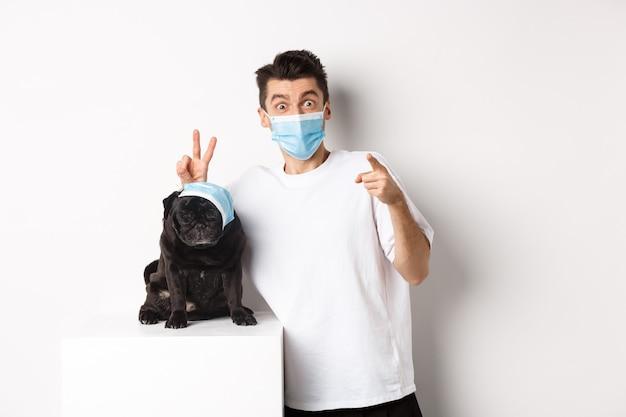 Covid-19, animali e concetto di quarantena. proprietario di cane felice e carlino carino indossando maschere mediche, uomo che punta il dito verso la telecamera e facendo divertenti orecchie da coniglio su animali, bianco