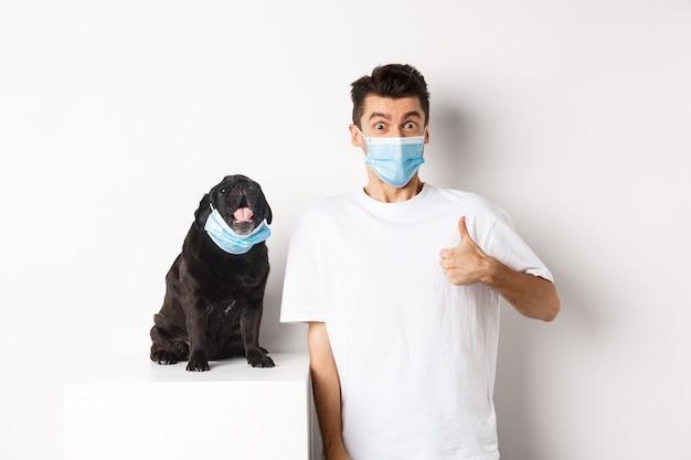 Covid-19, animali e concetto di quarantena. immagine del giovane divertente e del piccolo cane in mascherine mediche, proprietario che mostra il pollice in su in approvazione, elogia qualcosa, bianco