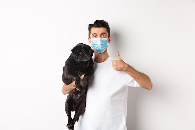 Covid-19, animali e concetto di quarantena. il giovane nella mascherina medica che tiene il cane nero sveglio del carlino, mostra il pollice in su, gradice e approva, stante sopra il bianco