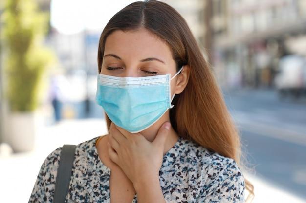 Covid-19 primo piano donna che indossa una maschera chirurgica con mal di gola all'aperto.