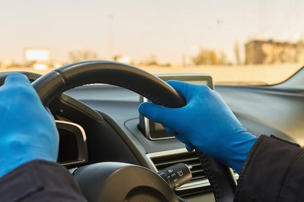 Concetto di covid-19. l'uomo guida un'auto in guanti medici protettivi blu.