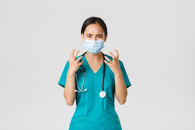 Covid-19, malattia da coronavirus, concetto di operatori sanitari. medico femminile asiatico arrabbiato e incazzato, medico in maschera medica e scrub, pugni stretti indignati, che sembra furioso, sfondo bianco.