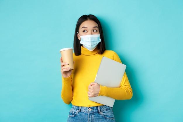 Covid-19, assistenza sanitaria e concetto di quarantena. studentessa asiatica in maschera medica in piedi con il computer portatile e caffè dal caffè, in piedi su sfondo blu.