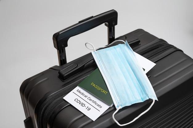 Un certificato sanitario covid-19, passaporto e maschera medica su una valigia nera. post-covid-19 concetto di business.