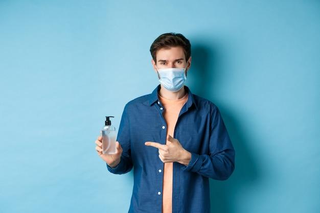 Covid-19, concetto di salute e pandemia. uomo sorridente nella mascherina medica che mostra disinfettante per le mani, raccomandando la bottiglia antisettica, sfondo blu.