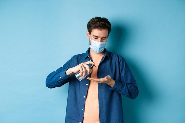 Covid-19, concetto di salute e pandemia. giovane ragazzo in mascherina medica che pulisce le mani con disinfettante, applica l'antisettico sul palmo, in piedi su sfondo blu.