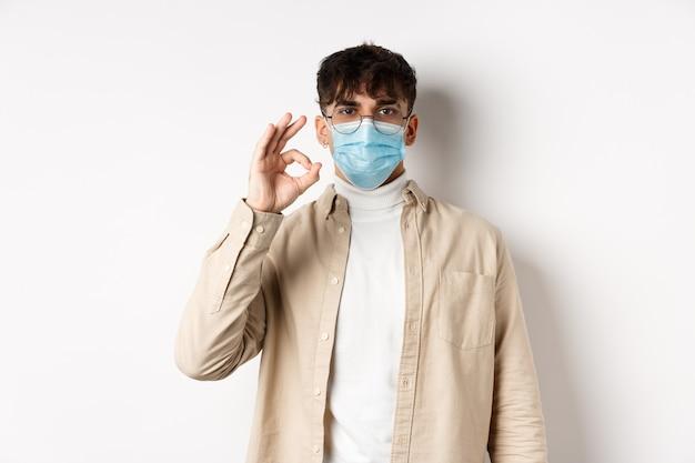 Covid-19, salute e concetto di persone reali. il ragazzo naturale con gli occhiali e la mascherina medica mostra il segno giusto, accetta o approva qualcosa, in piedi sul muro bianco.