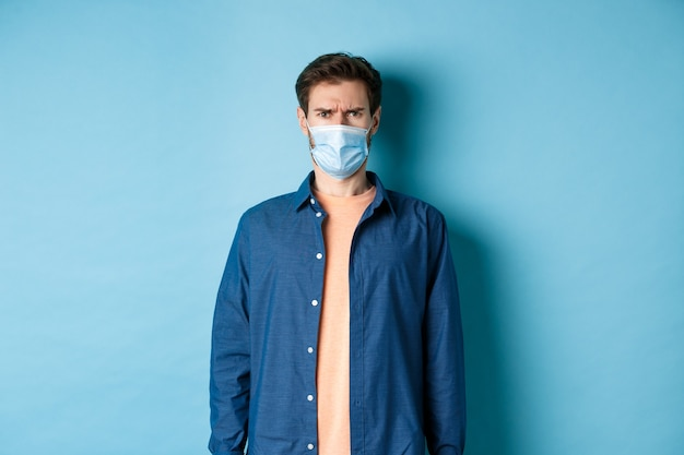 Covid-19 e concetto di assistenza sanitaria. ragazzo deluso in maschera medica accigliato, guardando confuso, in piedi su sfondo blu.