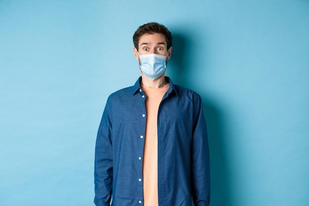 Covid-19 e concetto di assistenza sanitaria. immagine del bel ragazzo moderno in maschera per il viso alzando le sopracciglia per la sorpresa, guardando qualcosa in soggezione, sfondo blu.