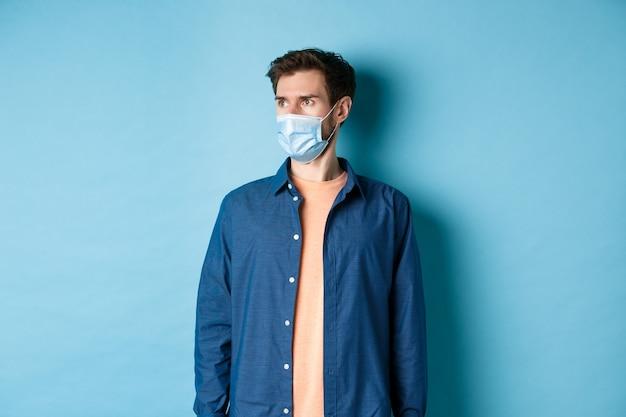Covid-19 e concetto di assistenza sanitaria. giovane scioccato nella mascherina medica che osserva da parte lo spazio vuoto su priorità bassa blu.