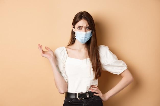 Covid-19 e concetto di stile di vita. ragazza confusa in mascherina medica aggrottando le sopracciglia, indicando a sinistra con lamentela, delusa da qualcosa di brutto, in piedi contro il beige.