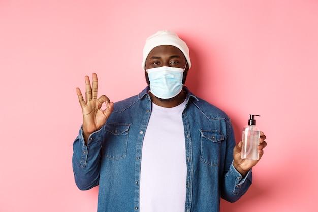 Covid-19, stile di vita e concetto di blocco. bel ragazzo hipster afroamericano in maschera facciale e berretto, che mostra disinfettante per le mani e segno ok, consiglio di usare antisettico.