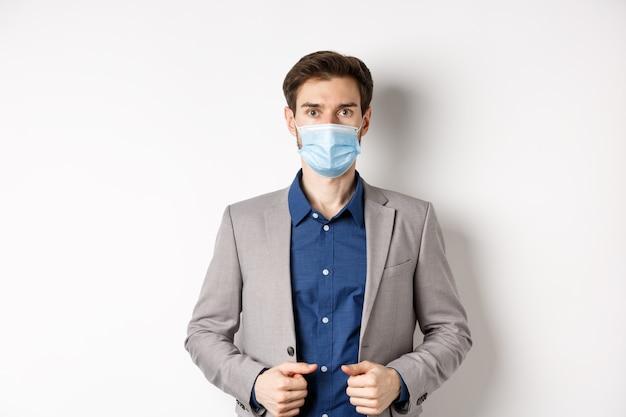 Covid-19 e concetto di impiegati. fiducioso uomo d'affari in maschera medica e tuta guardando la fotocamera, in piedi su sfondo bianco.