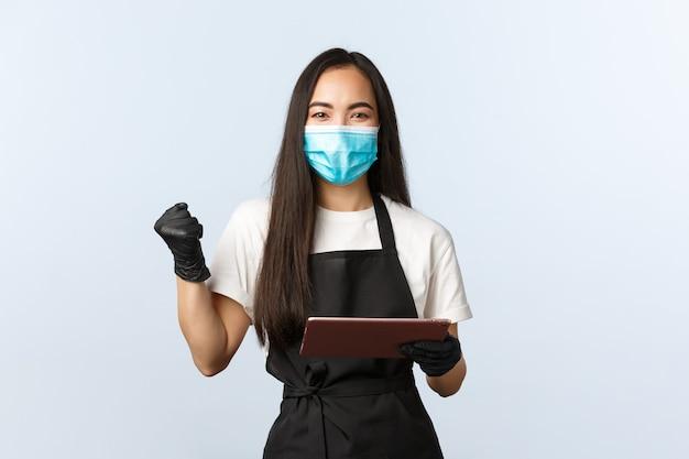 Covid-19, ordini online, piccola caffetteria e prevenzione del concetto di virus. soddisfatto esultanza barista donna asiatica, pompa pugno lavoratore caffè come utilizzando tablet digitale, indossare maschera medica.