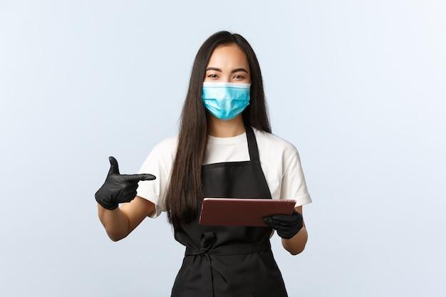 Covid-19, ordini online, piccola caffetteria e prevenzione del concetto di virus. sorridente barista asiatico, cameriera in maschera medica e guanti che puntano al tablet digitale, prendendo l'ordine del consumatore.