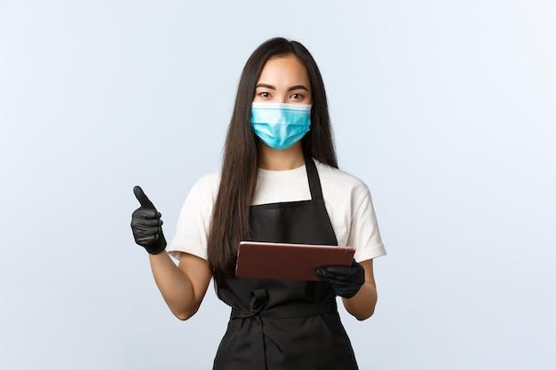 Covid-19, ordini online, piccola caffetteria e prevenzione del concetto di virus. sorridente barista asiatica carina in grembiule, maschera medica e guanti, mostra il pollice in su, prendi l'ordine con la tavoletta digitale