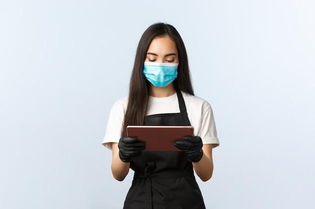 Covid-19, ordini online, piccola caffetteria e prevenzione del concetto di virus. giovane cameriera in maschera medica che guarda la tavoletta digitale mentre prende l'ordine dal visitatore del caffè, barista al lavoro.