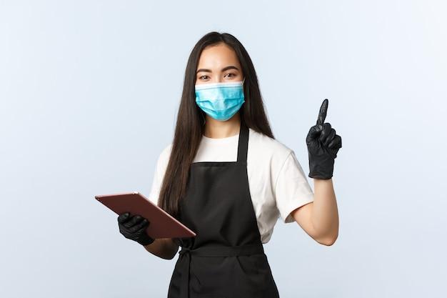 Covid-19, ordini online, piccola caffetteria e prevenzione del concetto di virus. la cameriera asiatica sorridente e amichevole, la barista in maschera medica e i guanti puntano l'angolo in alto a destra, usano la tavoletta digitale