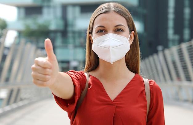 Covid-19 donna d'affari ottimista che indossa la maschera protettiva kn95 ffp2 che mostra i pollici in su nella strada della città moderna