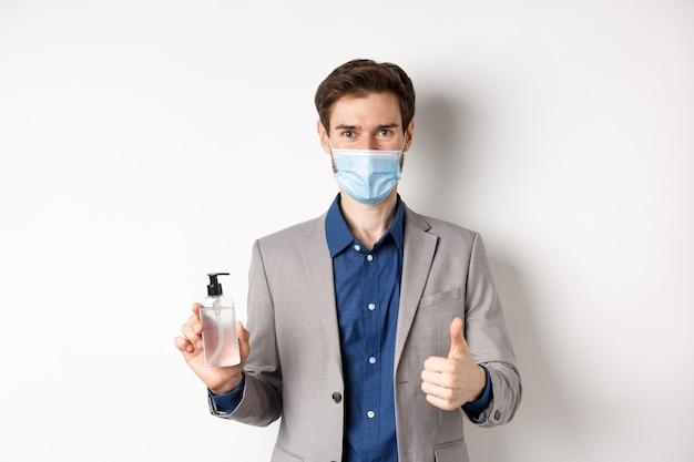 Covid-19, pandemia e concetto di business. uomo d'affari in tuta da ufficio e maschera medica che mostra una bottiglia di disinfettante per le mani e pollice in su, consiglia di utilizzare un antisettico al lavoro.