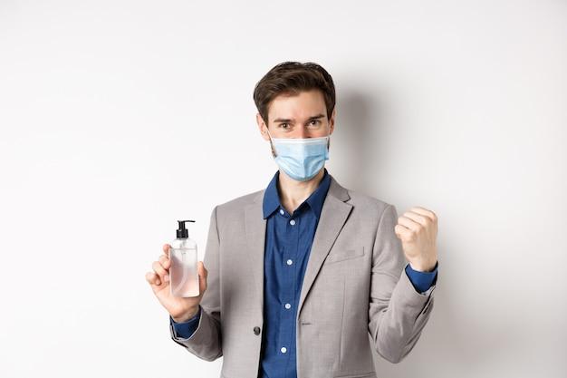Covid-19, pandemia e concetto di business. allegro ragazzo dell'ufficio in maschera medica e tuta, cercando motivato, mostrando una bottiglia di antisettico, sfondo bianco.