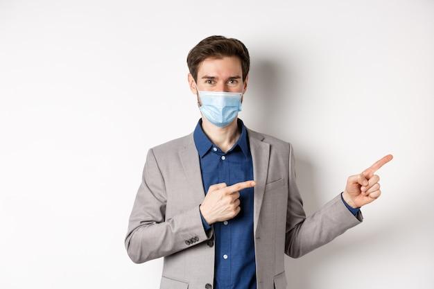 Covid-19, pandemia e concetto di business. fiducioso manager maschio in tuta e maschera medica che mostra il modo, puntando le dita a destra alla pubblicità, sfondo bianco.