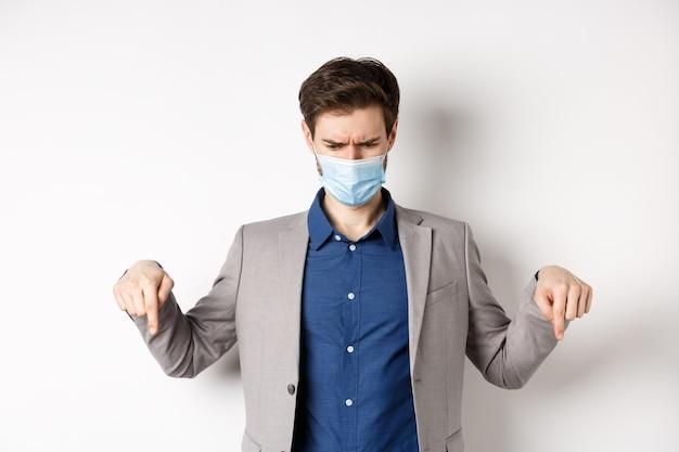 Covid-19, pandemia e concetto di business. uomo d'affari confuso e scontento nella mascherina medica che aggrotta le sopracciglia, punta il dito verso il basso e sembra deluso, sfondo bianco.