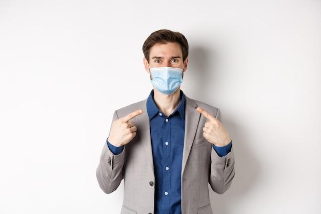 Covid-19, pandemia e concetto di business. eccitato uomo d'affari in tuta che punta alla sua maschera medica e sorridente con gli occhi, sfondo bianco.