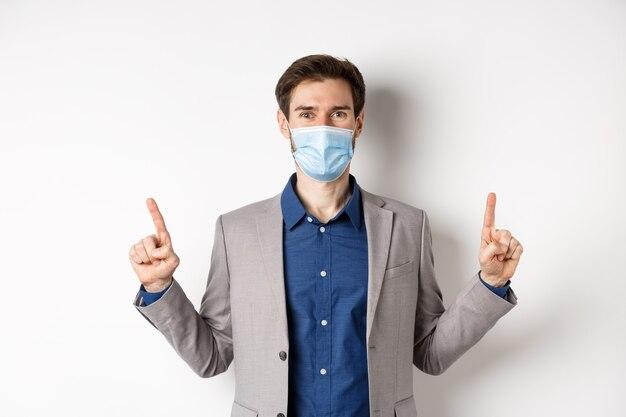 Covid-19, pandemia e concetto di business. felice imprenditore in maschera medica e tuta puntando le dita verso l'alto, in piedi su sfondo bianco.
