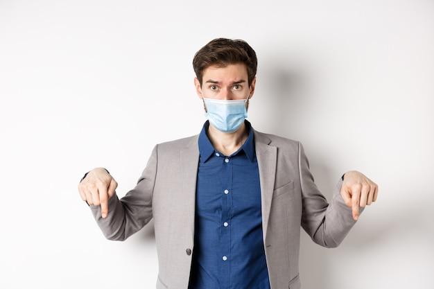 Covid-19, pandemia e concetto di business. esitante uomo in tuta e mascherina medica chiedendo parere, puntando il dito verso il basso e guardare la fotocamera, sfondo bianco.