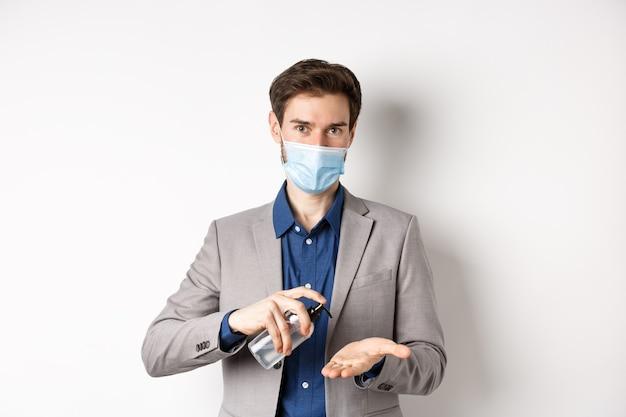 Covid-19, pandemia e concetto di business. impiegato maschio pulire le mani con antisettico, utilizzando disinfettante e guardando la telecamera, indossando una maschera medica.