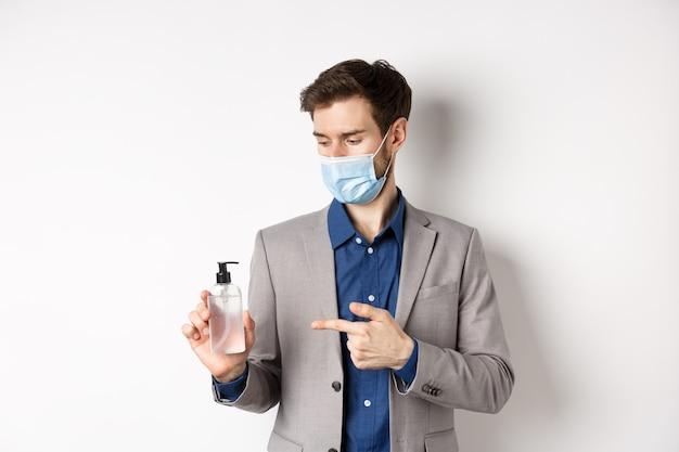 Covid-19, pandemia e concetto di business. impiegato nella mascherina medica che indica alla bottiglia di disinfettante per le mani, utilizzando un antisettico al lavoro, sfondo bianco.
