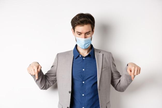 Covid-19, pandemia e concetto di business. ragazzo sorpreso in maschera medica e vestito che guarda e punta verso il basso con gli occhi schioccati, ansimante stupito, sfondo bianco.
