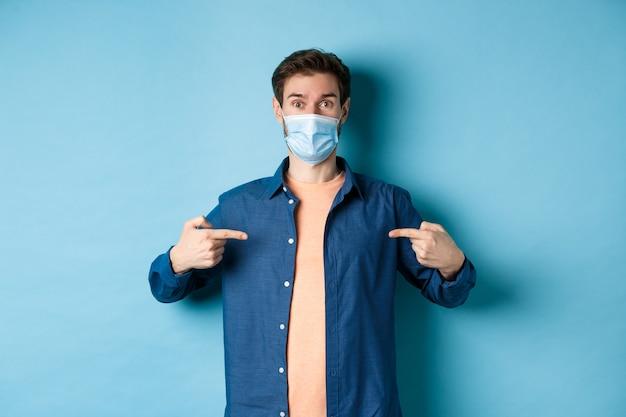 Covid-19 e il concetto di pandemia. giovane in buona salute nella mascherina medica che punta le dita al logo centrale, in piedi su sfondo blu.