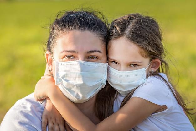 Concetto di pandemia di covid-19. ritratto di giovane madre e figlia piccola all'aperto che indossa maschere mediche.