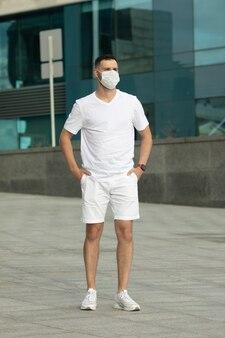 Covid-19 pandemia coronavirus uomo in strada cittadina che indossa una maschera protettiva per la diffusione della malattia da coronavirus 2019.