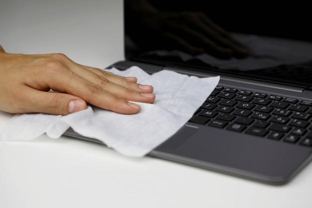 Covid-19 pandemia coronavirus donna disinfetta la tastiera del laptop con salviettine umidificate pulizia dello schermo del telefono intelligente contro la malattia da coronavirus 2019 focolaio