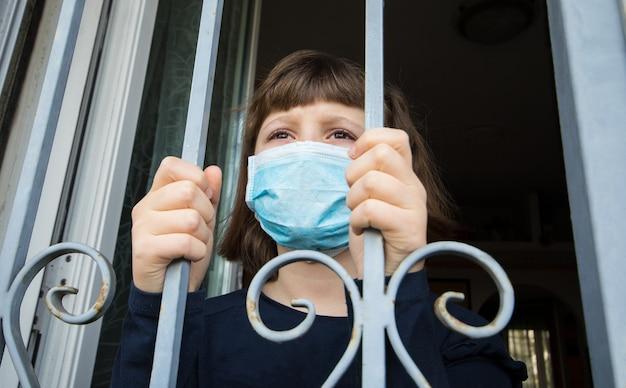 Covid-19 pandemia coronavirus ragazza in isolamento domiciliare quarantena automatica che indossa una maschera facciale che guarda fuori dalle finestre