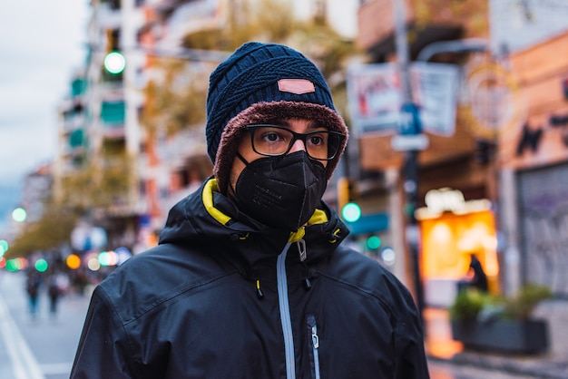 Covid-19 coronavirus pandemico giovane uomo che indossa abiti invernali in una strada cittadina con maschera facciale