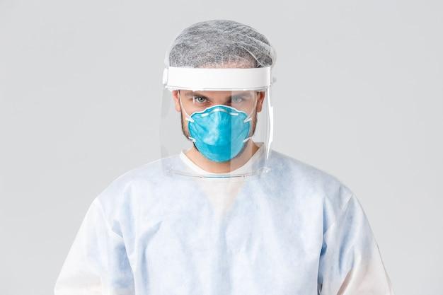 Covid-19, pandemia, operatori sanitari che combattono l'epidemia di virus. volto di un medico serio in battaglia contro il coronavirus, indossando visiera, maschera medica e tuta protettiva personale, guarda la telecamera determinata