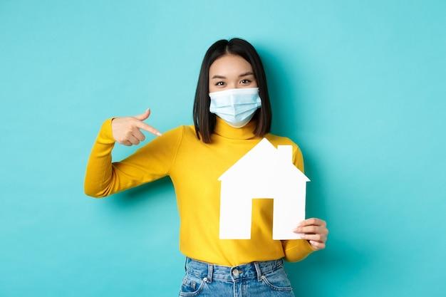 Covid-19, pandemia e concetto immobiliare. la donna asiatica allegra che sorride nella mascherina medica, mostrando il ritaglio della casa di carta, consiglia l'agenzia per l'acquisto della proprietà, fondo blu.