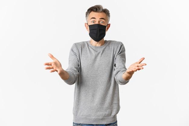 Covid-19, concetto di pandemia e allontanamento sociale. ritratto dell'uomo di mezza età spaventato nella mascherina medica nera