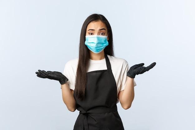 Pandemia di covid-19, distanza sociale, piccole imprese e prevenzione del concetto di virus. barista asiatica inconsapevole e perplessa in maschera medica e guanti che si stringono nelle spalle, non lo so, non posso dirlo, non essendo a conoscenza