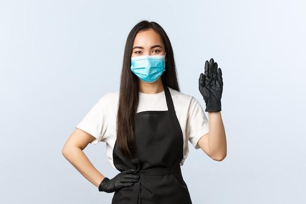 Pandemia di covid-19, distanza sociale, piccole imprese e prevenzione del concetto di virus. amichevole barista femminile in maschera medica e guanti che saluta i clienti, dà il benvenuto al consumatore e prende l'ordine al bar