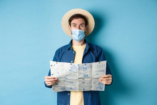 Covid-19, pandemia e concetto di viaggio. il turista in maschera medica sembra sorpreso, tenendo la mappa, in piedi su sfondo blu.