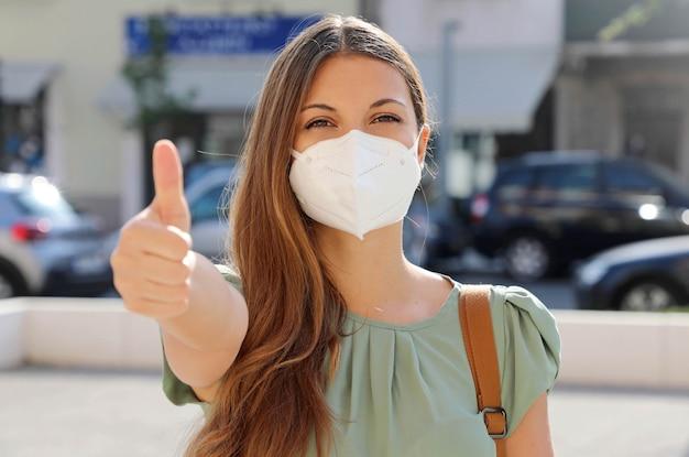 Covid-19 giovane donna positiva che indossa la maschera protettiva ffp2 che evita il coronavirus 2019 che mostra i pollici in su in una strada cittadina