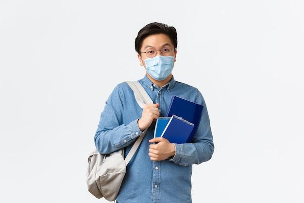 Covid-19, prevenzione del virus e distanza sociale al concetto universitario. studente maschio asiatico uscente spensierato, ragazzo in maschera medica e occhiali che conversano, tiene zaino e quaderni.