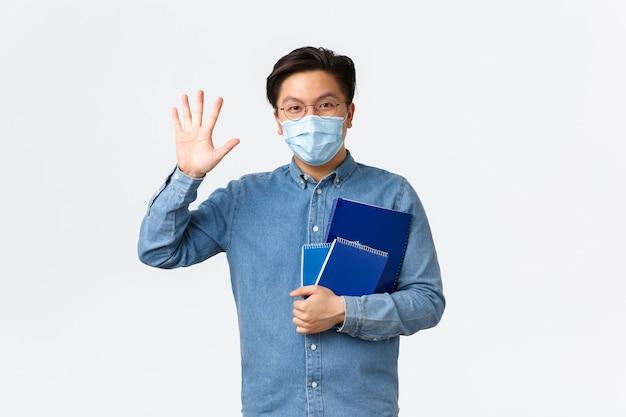 Covid-19, prevenzione del virus e distanza sociale al concetto universitario. amichevole studente maschio asiatico sorridente che saluta, agitando la mano in un gesto di saluto, porta quaderni, indossa maschera medica e occhiali.